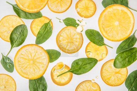 juicy orange slices with green spinach leaves on grey background