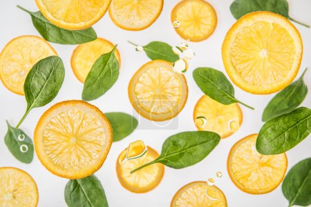 fresh juicy orange slices with green spinach leaves on grey background with water bubbles