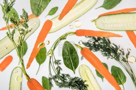 fondo con zanahorias, pepinos en rodajas, hojas de espinaca y burbujas de agua