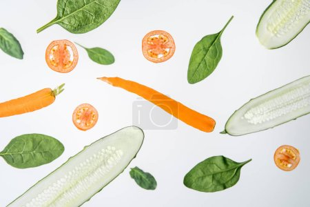 Photo for Sliced cucumbers, tomatoes, carrots and green spinach leaves on grey background - Royalty Free Image
