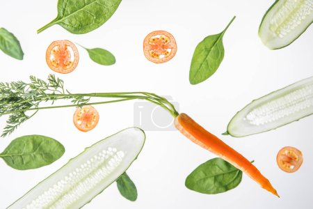 Photo for Sliced cucumbers, tomatoes, carrot and spinach leaves on grey background - Royalty Free Image
