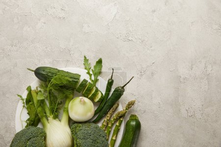 Photo for Top view of fresh vegetables on grey textured surface - Royalty Free Image