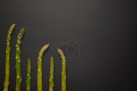 Photo for Top view of fresh green asparagus on black surface - Royalty Free Image
