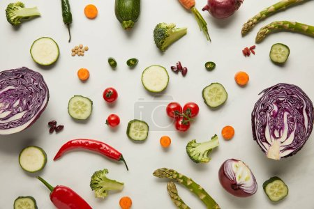 Photo for Top view of cutlery, vegetables and seeds on white surface - Royalty Free Image