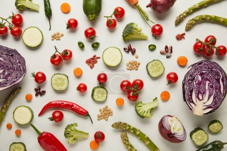 Top view of cutlery, vegetables and seeds on white surface