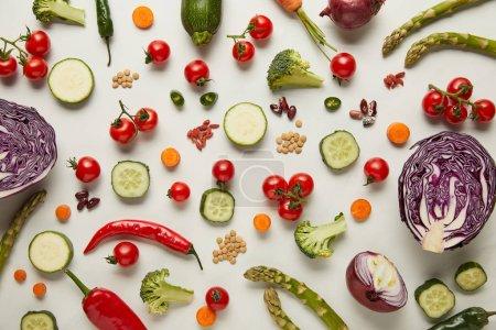 Vista superior de cubiertos, verduras y semillas en la superficie blanca
