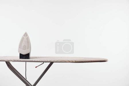 Photo for Ironing board with dark legs and iron isolated on grey - Royalty Free Image