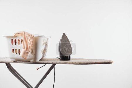 Photo for Ironing board, laundry basket and iron isolated on white - Royalty Free Image