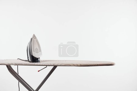 Photo for Ironing board with dark legs and iron isolated on white - Royalty Free Image