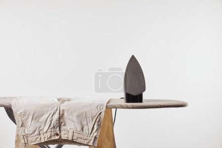 Photo for Ironing board, beige pants and iron isolated on grey - Royalty Free Image
