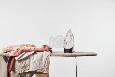 Photo for Clothes and iron on ironing board isolated on grey - Royalty Free Image