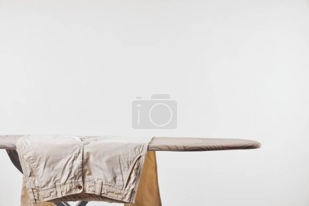 Photo for Beige male pants on ironing board isolated on grey - Royalty Free Image