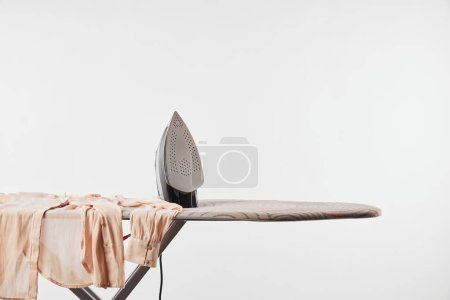 Photo for Shirt and iron on ironing board isolated on grey - Royalty Free Image