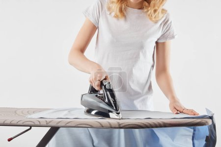 Cropped view of girl ironing blue shirt isolated on white