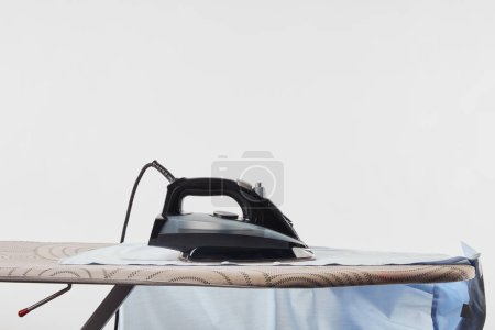 Photo for Iron and blue shirt on ironing board isolated on white - Royalty Free Image