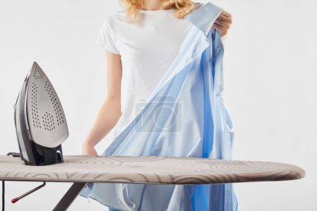 Photo for Cropped view of girl ironing blue shirt isolated on white - Royalty Free Image