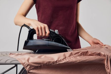 Photo for Cropped view of woman with black iron ironing shirt isolated on grey - Royalty Free Image