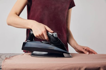 Cropped view of woman with black iron ironing shirt isolated on grey