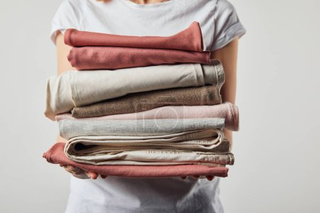 Photo for Cropped view of woman holding folded ironed clothes isolated on grey - Royalty Free Image