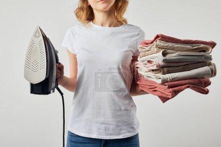 Photo pour Femme partielle en t-shirt tenant du fer et des vêtements repassés pliés isolés sur gris - image libre de droit
