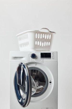 Washing machine with laundry basket isolated on grey
