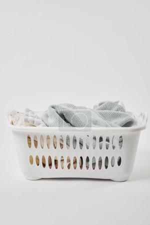 Foto de Cesta de lavandería de plástico blanco con ropa sucia en gris - Imagen libre de derechos
