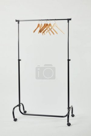 Photo for Black steel straight rack with wooden hangers on grey - Royalty Free Image
