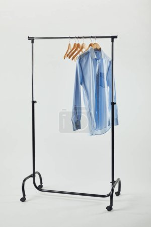 Photo for Straight rack, wooden hangers and blue shirt isolated on grey - Royalty Free Image