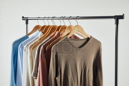 Foto de Cremallera recta, colgadores de madera y ropa masculina aislada en gris - Imagen libre de derechos