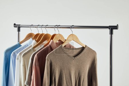 Photo for Straight rack, wooden hangers and male clothes isolated on grey - Royalty Free Image