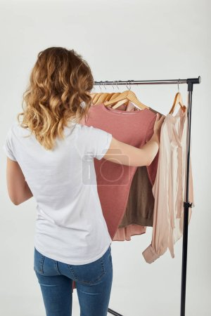 Photo for Back view of girl hanging hangers with clothes on straight rack on grey - Royalty Free Image