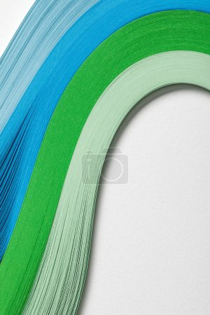close up of wavy blue and green paper lines on grey background