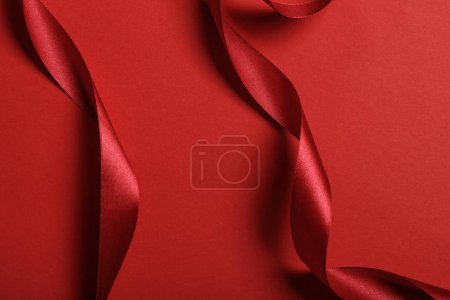 Photo pour Gros plan de rubans courbes en soie rouge sur fond rouge - image libre de droit