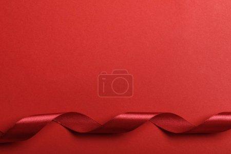 Photo pour Vue de dessus des courbes de ruban de soie rouge sur fond rouge - image libre de droit