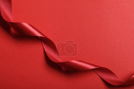 Photo for Top view of curved silk red ribbon on red background with copy space - Royalty Free Image