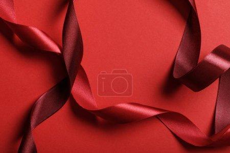 Photo pour Gros plan de rubans bordeaux et rouges en soie incurvée sur fond rouge - image libre de droit