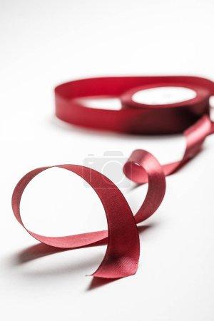 Photo pour Focus sélectif du ruban bordeaux ondulé de soie avec bobine sur fond gris - image libre de droit