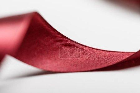 Photo pour Gros plan de ruban bordeaux courbé en soie brillante sur fond gris - image libre de droit
