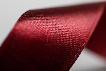 close up of shiny satin wavy burgundy ribbon on grey background