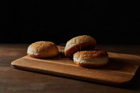 Photo for Fresh tasty buns with sesame on wooden chopping board isolated on black - Royalty Free Image