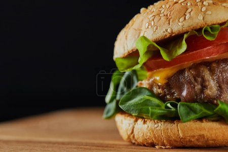 Photo for Close up of delicious meat burger with cheese, greenery and sesame isolated on black - Royalty Free Image