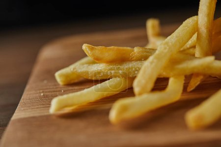 Photo for Close up of fresh golden french fries on wooden chopping board - Royalty Free Image