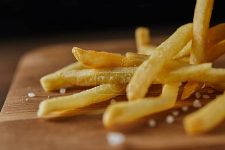 Photo for Close up of fresh golden french fries with salt on wooden chopping board - Royalty Free Image