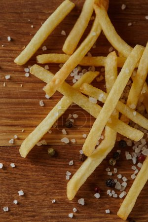 top view of salt, black pepper and golden french fries on wooden chopping board