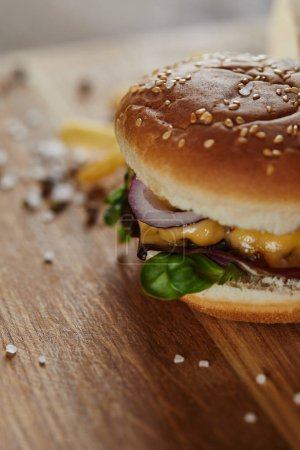 selective focus of salt, pepper and fresh burger on wooden surface