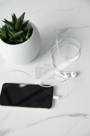 Photo for Earphones connected to smartphone with blank screen, and flowerpot on white marble surface - Royalty Free Image