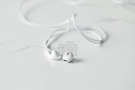 Photo pour Mise au point sélective d'écouteurs blancs câblés sur la surface blanche avec espace de copie - image libre de droit
