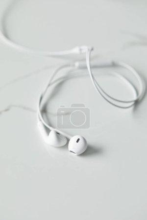 Photo pour Mise au point sélective des écouteurs blancs sur la surface blanche avec espace de copie - image libre de droit