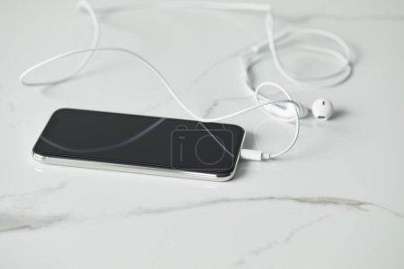 Photo pour Mise au point sélective du smartphone avec des écouteurs connectés sur la surface en marbre blanc - image libre de droit