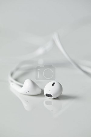 Photo for Selective focus of white wired earphones on white surface with copy space - Royalty Free Image